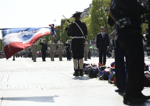 French President Francois Hollande (R) pays his respect at the Tomb of the Unknown Soldier at the base of the Arc de Triomphe during a ceremony marking the 71st anniversary of the victory over Nazi Germany during World War II on May 8, 2016 in Paris