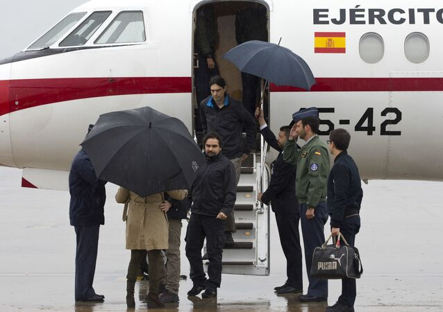 In this photo made available by Presidencia del Gobierno on Sunday, May 8, 2016, Spanish journalists Jose Manuel Lopez and Angel Sastre, center, arrive at the Torrejon military airbase in Madrid, Spain