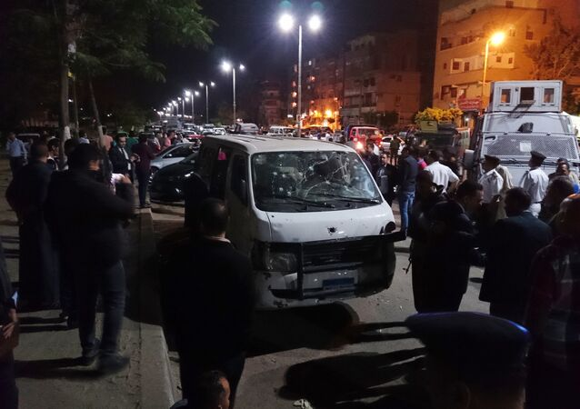 Egyptian police and civilians gather around a bullet ridden microbus in the south Cairo neighborhood of Helwan, Sunday, May 8, 2016