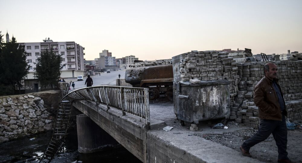 People walk past a burned truck at the entrance of Nusaybin on December 24, 2015, in Mardin