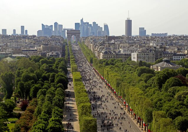 People walk on the car-free Champs-Elysees avenue in Paris, France, May 8, 2016