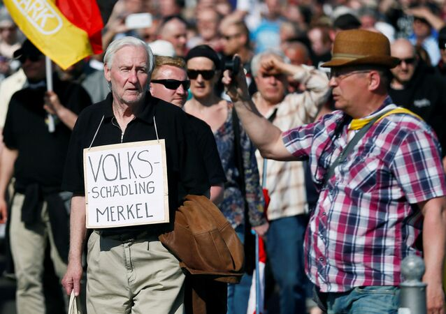 Right-wing protestors demonstrate against refugees, Islam and German Chancellor Angela Merkel in Berlin, Germany, May 7, 2016. The sign reads: Volksschaedling (Enemy of the People)