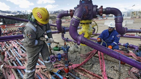 In this March 29, 2013, file photo, workers tend to a well head during a hydraulic fracturing operation outside Rifle, in western Colorado - Sputnik International