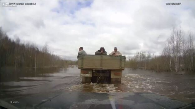 Truck Tows Lada Niva on Flooded Road in Russia