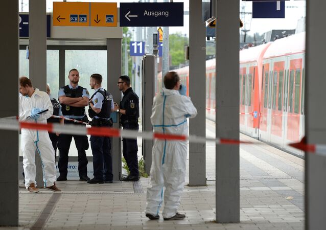 Forensic experts of the police stand next to a commuter train standig on a platform of the train station of Grafing near Munich, southern Germany, where a man killed one person and wounded three others in a knife attack on May 10, 2016