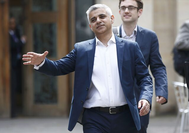 London's Mayor elect, Sadiq Khan, goes to shake hands with a passer-by as he leaves Southwark Cathedral in London, Britain, May 7, 2016.