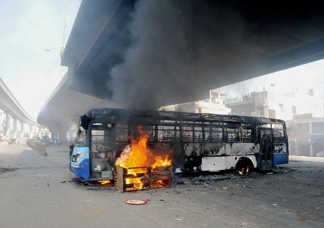 A bus burns underneath an flyover following a protest by Indian garment factory workers in Bangalore on April 19, 2016