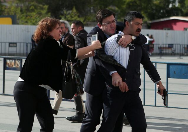 An assailant who attempted to shoot prominent Turkish journalist Can Dundar is caught by Dilek Dundar, wife of Can Dundar, and an unidentified man outside a courthouse in Istanbul, Turkey May 6, 2016