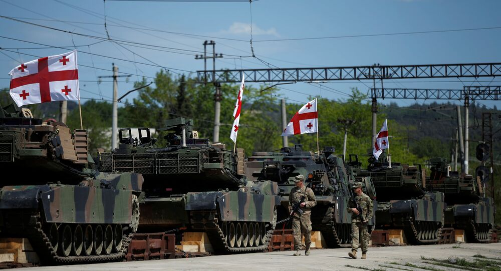 U.S. servicemen walk past U.S. M1A2 Abrams tanks as they arrive for the joint U.S.-Georgian exercise Noble Partner 2016 in Vaziani, Georgia, May 5, 2016