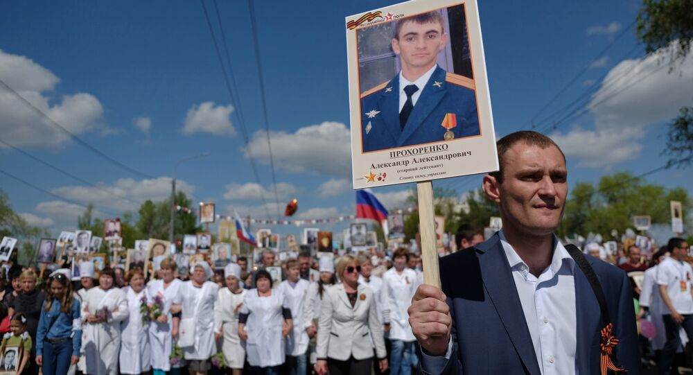 A participant carries a photo of Hero of Russia Alexander Prokhorenko killed in Syria, during the Immortal Regiment march on the 71st anniversary of Victory in Great Patriotic War (1941-1945) in Orenburg