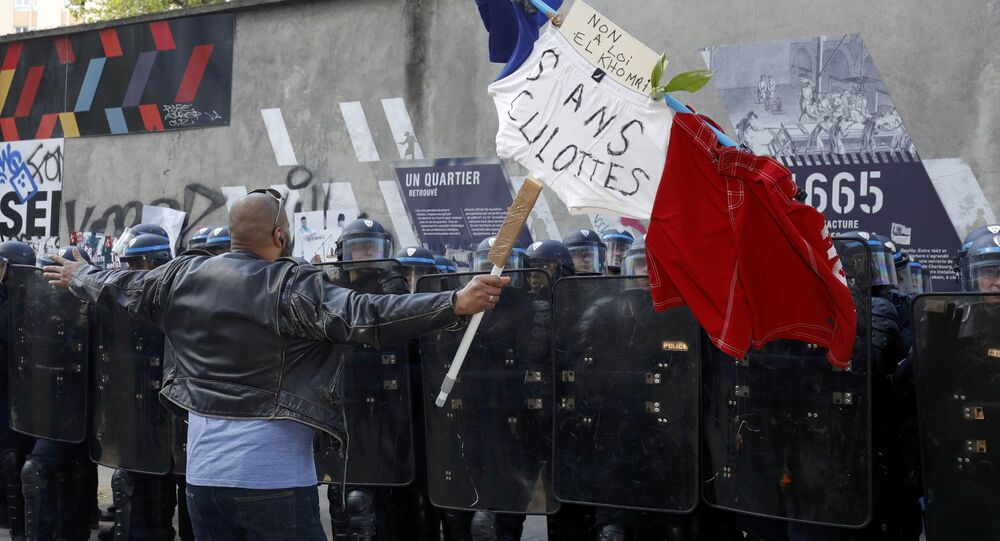 A man holds a French flag with the message, No to the El Khomri law in front of a line of French riot police during a protest against the French labour law proposal during the May Day labour union march in Paris, France, May 1, 2016.