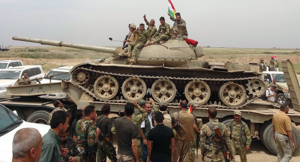 Iraqi Kurdish and Turkmen Shiite forces from the Popular Mobilisation units sit on top of a tank on May 1, 2016 in the northern Iraqi town of al-Bashir after they recaptured the town from the control of the Islamic State (IS) group
