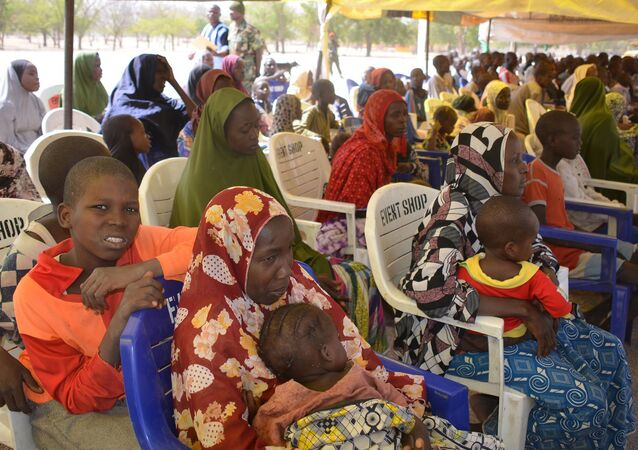 In this Feb. 12, 2016, file photo, woman and children detained by Nigeria army who have no links to Boko Haram sit under a canopy before their release at the Giwa military barracks in Maiduguri, Nigeria.