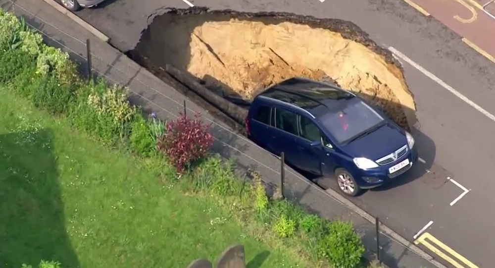 Car teeters on the edge of giant sinkhole, London
