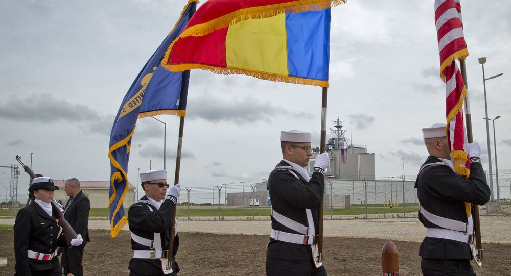 US Navy flag bearers, backdropped by the radar building of a missile defense base, walk in Deveselu, during an opening ceremony attended by U.S., NATO and Romanian officials at a base, originally established by the Soviet Union, in Deveselu, Southern Romania, Thursday, May 12, 2016.