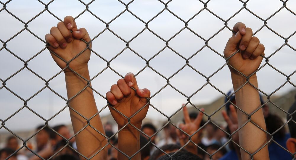 Syrian refugee children chant slogans behind a fence at the Nizip refugee camp in Gaziantep province, southeastern Turkey.