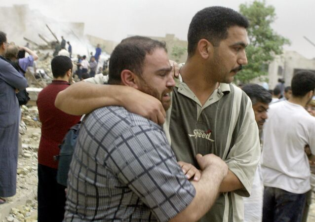 An Iraqi man (L) who lost nine members of his family in afternoon US-British coalition bombing of Baghdad's al-Mansur neighborhood grieves 07 April 2003 in the arms of a friend.