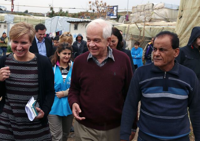 Canadian Minister of Immigration John McCallum, center, walks during his visit to a Syrian refugee camp.