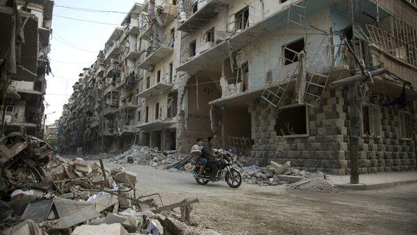 Syrian men ride a motorbike past damaged buildings in the rebel-held Bustan al-Qasr district in eastern Aleppo - Sputnik International