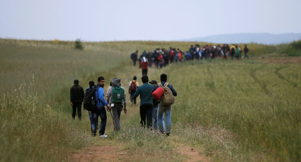 A group of migrants and refugees who stayed in Idomeni makeshift camp walks through a field in attempt to cross the Greek-Macedonian border near the village of Evzoni, Greece, May 12, 2016.