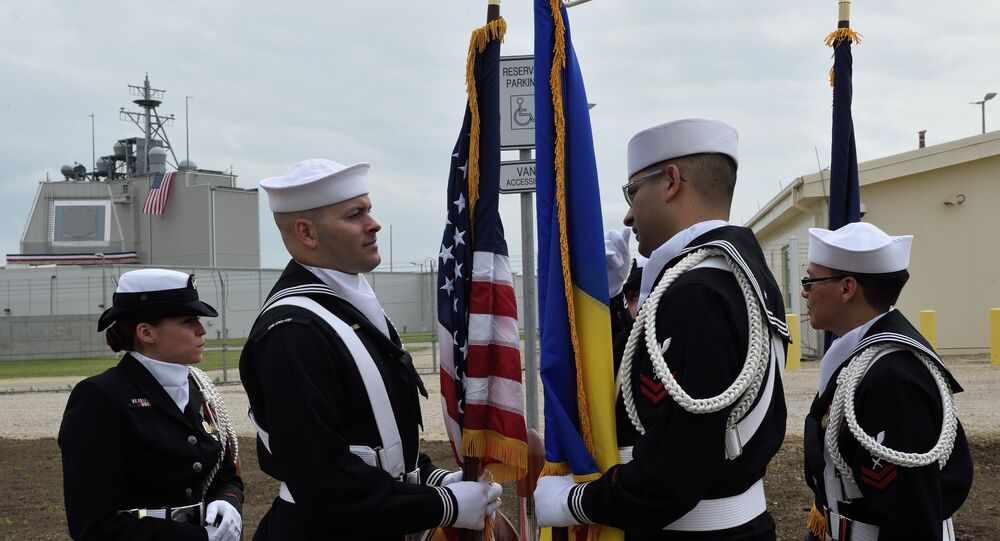 US Army personnel stand with the Romanian and the US flag during an inauguration ceremony of the US anti-missile station Aegis Ashore Romania (in the background) at the military base in Deveselu, Romania on May 12, 2016.