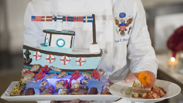 White House pastry chef Susie Morrison holds a dessert featuring a handcrafted fishing boat surrounded by miniature pastries during a press preview of a State Dinner in honor of the Nordic countries, including Sweden, Norway, Finland, Denmark and Iceland, in the State Dining Room of the White House in Washington, DC, May 12, 2016. - Sputnik International