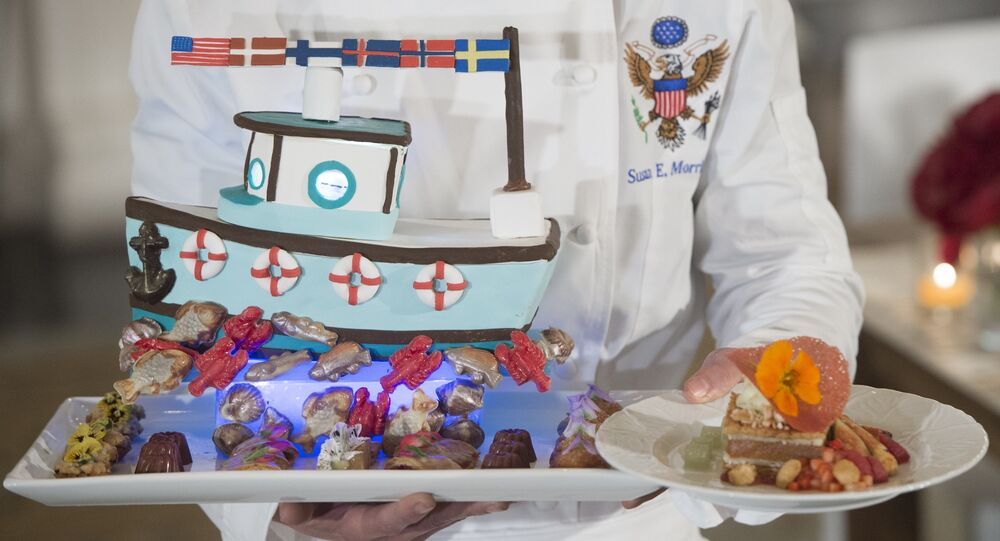 White House pastry chef Susie Morrison holds a dessert featuring a handcrafted fishing boat surrounded by miniature pastries during a press preview of a State Dinner in honor of the Nordic countries, including Sweden, Norway, Finland, Denmark and Iceland, in the State Dining Room of the White House in Washington, DC, May 12, 2016.