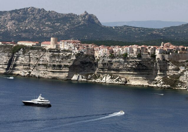 Boats sail off the cliffs of the city of Bonifacio, in the southern French Corsican island