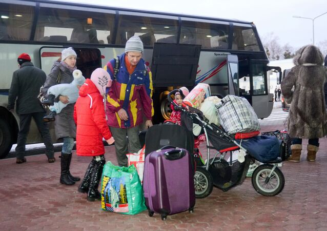 Refugees from Ukraine leave a bus at the airport of northeastern Ukrainian city of Kharkiv