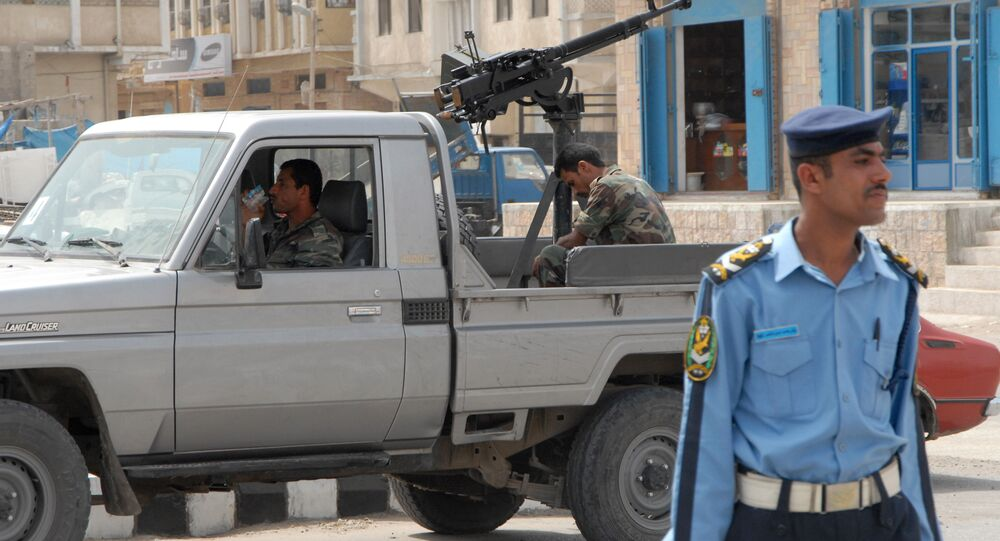 Yemeni policemen stand guard in the Yemeni city of Mukalla