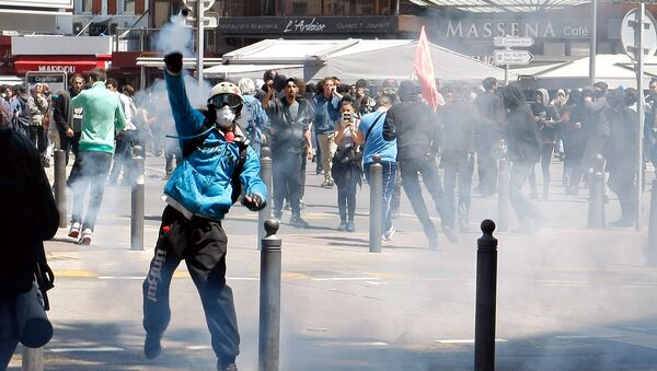 A masked demonstrator throws a tear gas canister during a clash with police, after a demonstration in Marseille, southern France, Thursday, May 12, 2016. - Sputnik International