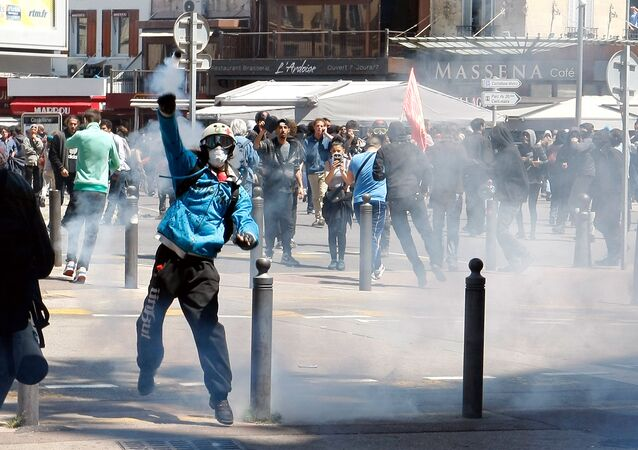 A masked demonstrator throws a tear gas canister during a clash with police, after a demonstration in Marseille, southern France, Thursday, May 12, 2016.