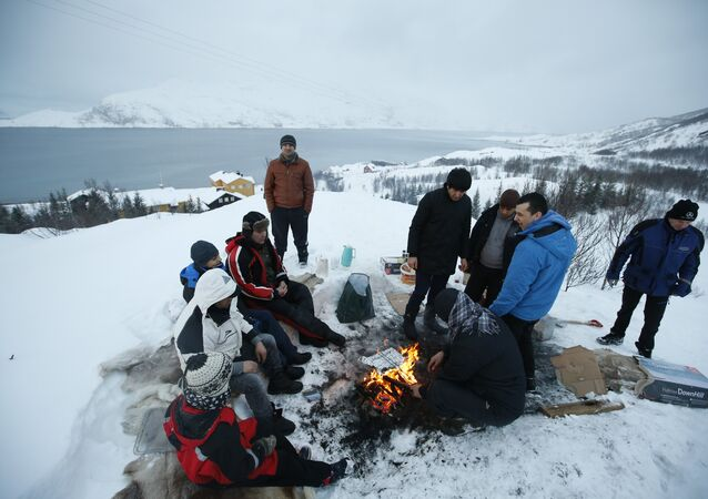 Asylum seekers gather round a fire as they cook a meal overlooking the temporary Altnes camp refugee camp on the island of Seiland, northern Norway (File)