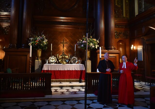 Father Anthony Howe (R) shows Archbishop of Westminster, Cardinal Vincent Nichols (L) around the Royal chapel ahead of a service at Hampton Court Palace, in south west London on February 9, 2016.