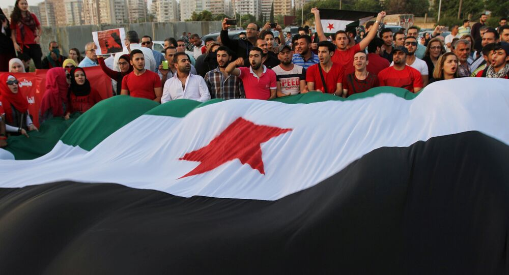 Syrian protesters hold a giant Syrian opposition flag (File)