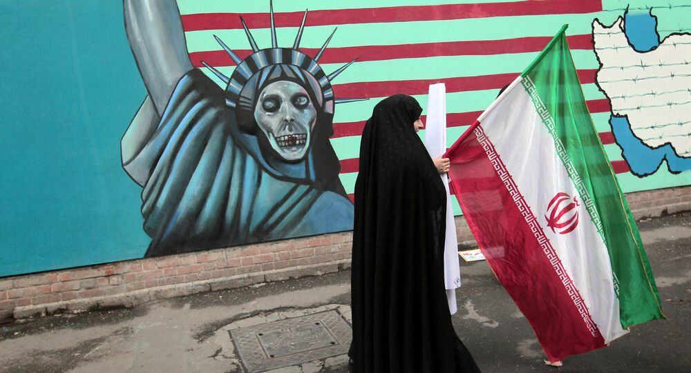 An Iranian woman holds her national flag as she walks past an anti-US mural depicting the Statue of Liberty on the wall of the former US embassy in Tehran (File)