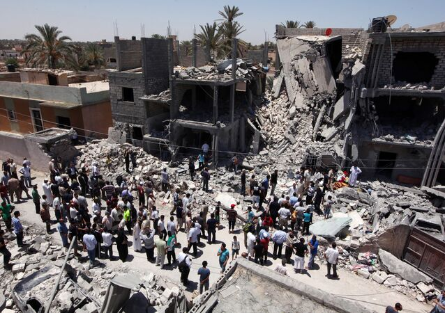 Libyans gather  next to the rubble of buildings the Libyan authorities said were damaged by airstrikes on Tripoli's residential district of Arada (File)