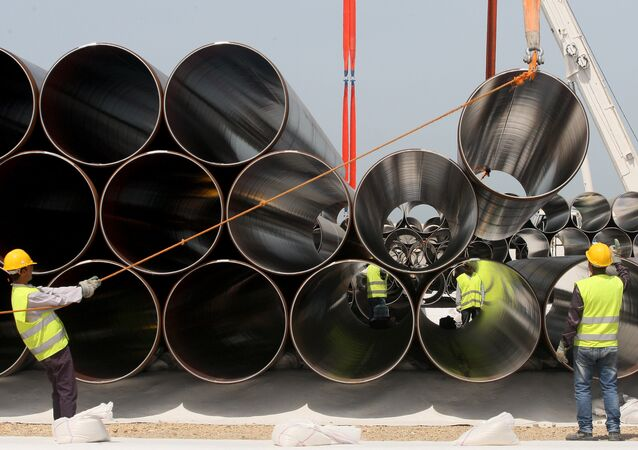 Workers unload newly arrived pipes for the construction of the future Trans-Adriatic Pipeline (File)