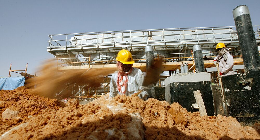 Asian labourers work at the site of Saudi Aramco's (the national oil company) central oil processing facility in al-Khurais, still under construction in the Saudi Arabian desert, 160 kms east of the capital Riyadh (File)