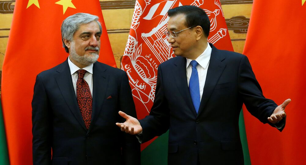 Chinese Premier Li Keqiang (R) talks with Afghan Chief Executive Officer Abdullah Abdullah at a signing ceremony at the Great Hall of the People in Beijing, China, May 16, 2016