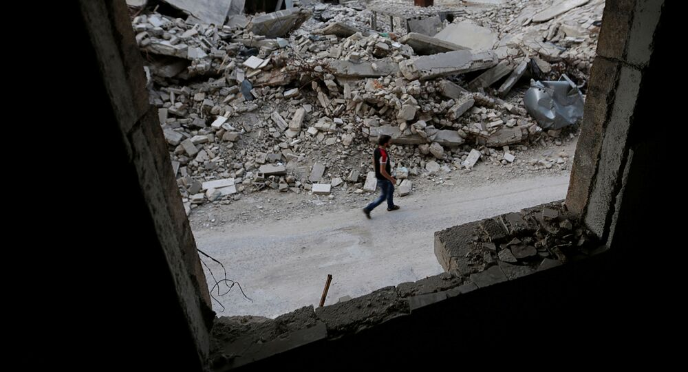 A man walks past damaged buildings in the rebel-controlled area of Maaret al-Numan town in Idlib province, Syria, May 15, 2016