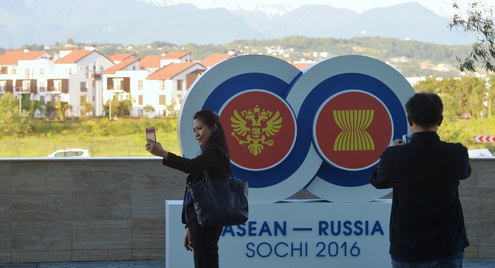 Holidaymakers take pictures with the ASEAN-Russia Summit logo near the Sochi Congress Center, which will be a venue of the ASEAN-Russia Summit