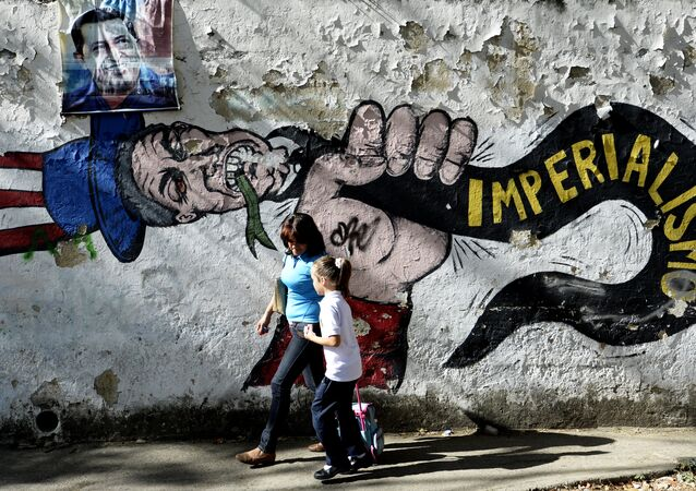 A woman and a girl walk in front of a graffiti of US Uncle Sam in Caracas on March 11, 2015