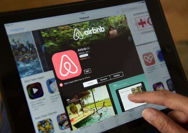 A woman browses the site of US home sharing giant Airbnb on a tablet in Berlin on April 28, 2016.