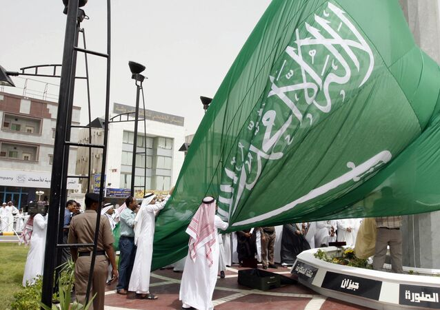 Saudi men unfurl a giant Saudi national flag during a ceremony to raise the highest flag in the country in the eastern city of Dammam on June 17, 2008