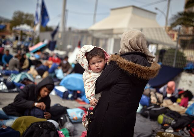 A Syrian woman holds her child at the port of Chios on April 3, 2016 as refugees and migrants who broke out from Chios detention camp, stand in the port of the city.
