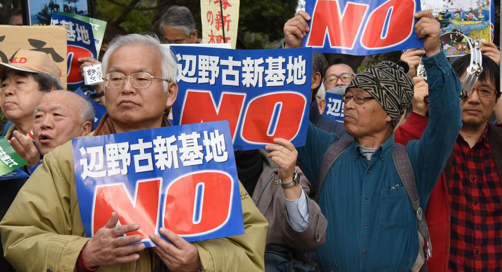 People hold banners as they listen to a speaker during a rally against a new US military base in Okinawa, Japan's nouthernmost prefecture (file)
