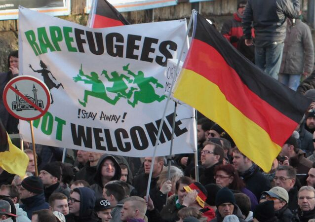 Right-wing demonstrators hold a sign Rapefugees not welcome - !Stay away! and a sign with a crossed out mosque as they march in Cologne, Germany