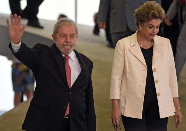 Former Brazilian president Luiz Inacio Lula da Silva (L) gestures next to Dilma Rousseff