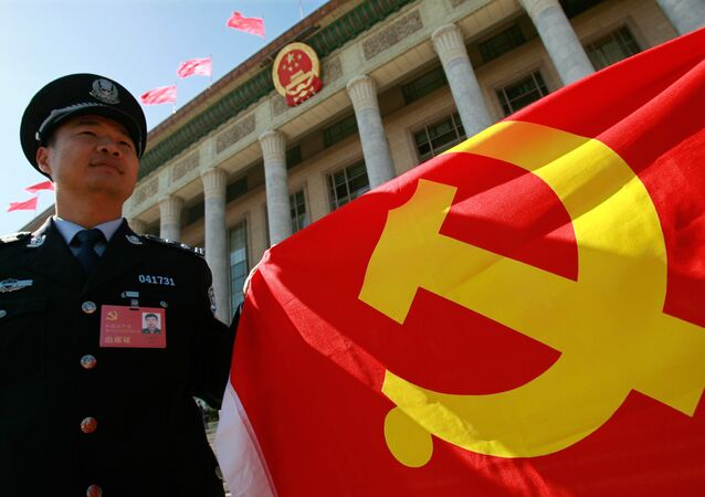 A Chinese policeman holds a Chinese Communist Party flag